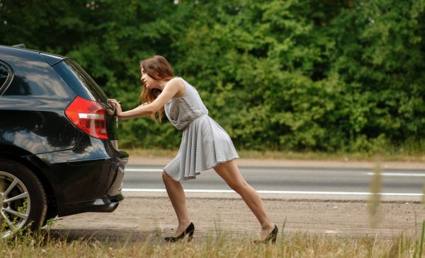 Woman pushing broken car on road, breakdown. Crashed automobile or emergency accident with vehicle, trouble with engine on highway
