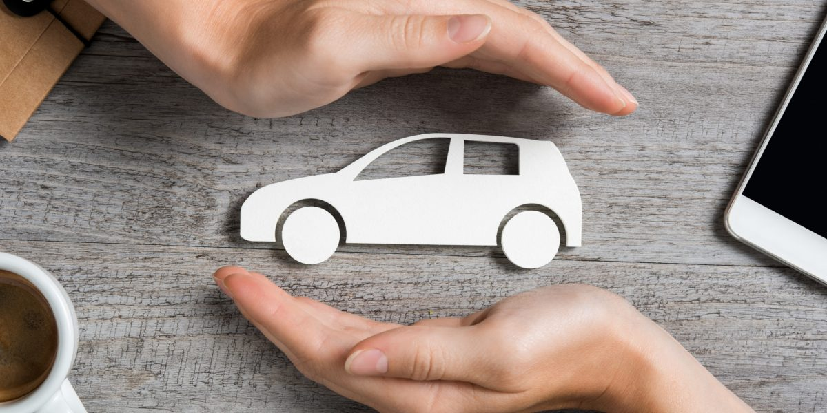Hands protecting icon of car over wooden table. Top view of hands showing gesture of protecting car. Car insurance and automotive business concept.