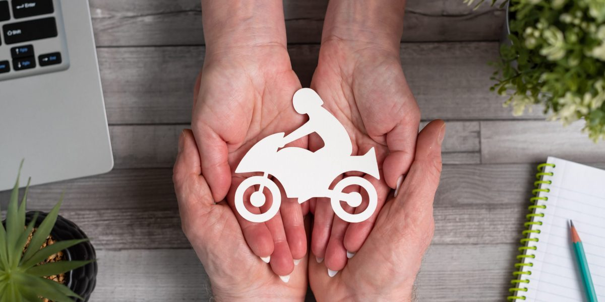 Concept of motorbike insurance with paper bike in hands